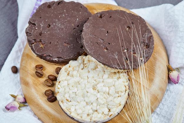 Cracker di riso e cioccolato su un piatto di legno con una tovaglia. Foto Gratuite