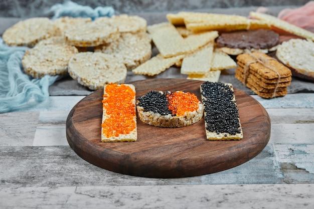 Cracker di riso con caviale rosso e nero su un piatto di legno. foto di alta qualità Foto Gratuite