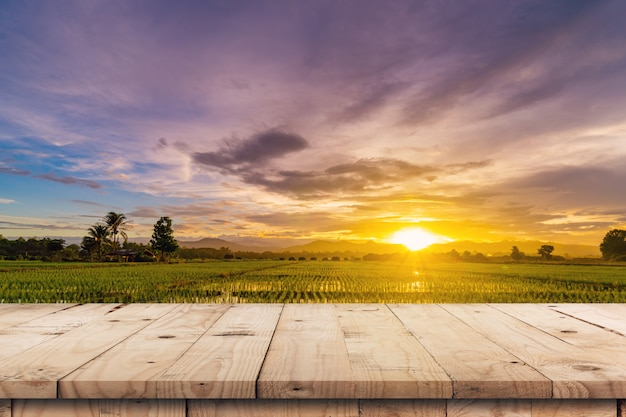 Rice field sunset and empty wood table for product display and montage. Premium Photo