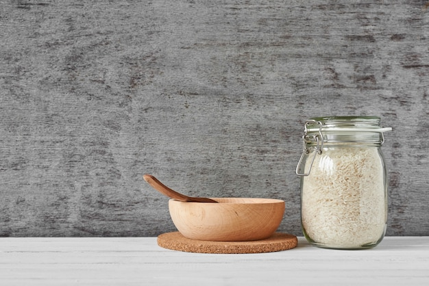 Rice grains in glass jar and wooden bowl Premium Photo
