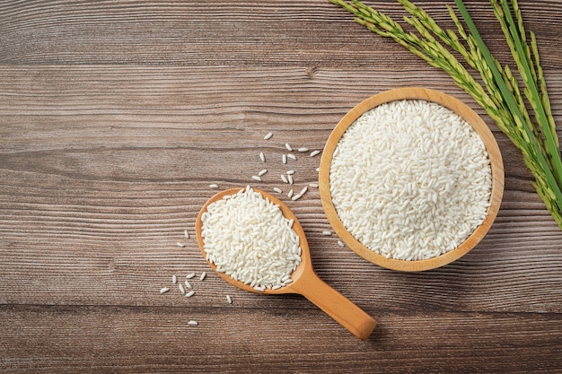 나무 그릇에 쌀과 쌀 식물을 가진 나무로되는 숟가락 무료 사진