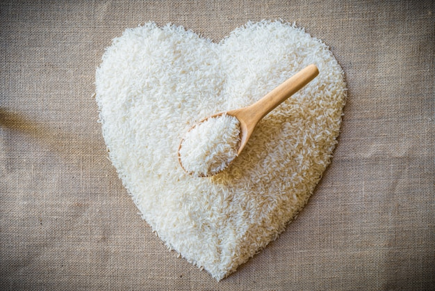 Rice laid out in a heart shape on sackcloth with wooden spoon Premium Photo