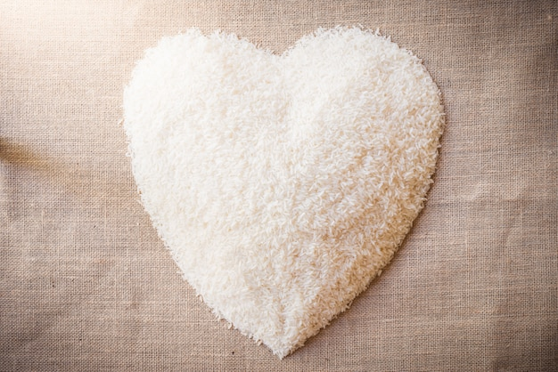 Rice laid out in heart shape on sackcloth Premium Photo