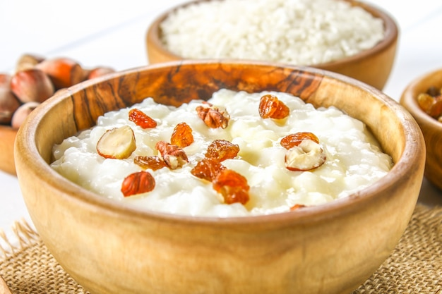 Rice milk porridge with nuts and raisins in wooden bowls on a white wooden table Premium Photo