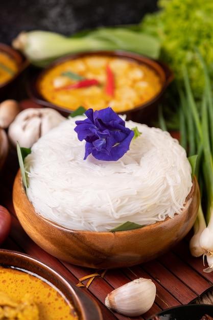Spaghetti di riso in una ciotola di pasta di curry con peperoncino, cetriolo, fagioli lunghi, lime, aglio e cipollotto Foto Gratuite