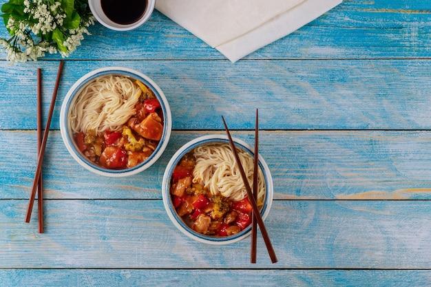 그릇과 젓가락에 닭고기와 야채를 볶은 쌀국수 프리미엄 사진
