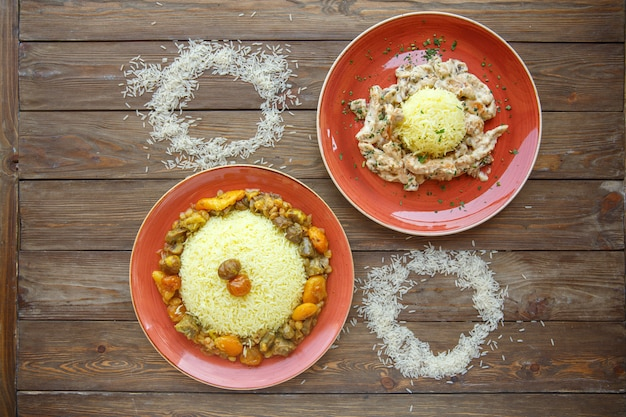 Rice plates with meat and dried fruits and creamy chicken and mushroom Free Photo