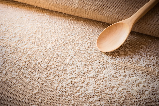 Rice on sackcloth and wooden spoon use for background Premium Photo