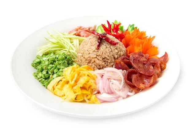 赤玉ねぎ、豆、マンゴー、目玉焼きのエビのペーストまたは米ミックススライスで味付けしたご飯、タイ料理スタイルのフュージョンは、白い背景に分離された切り分けられた野菜の側面図で飾る Premium写真