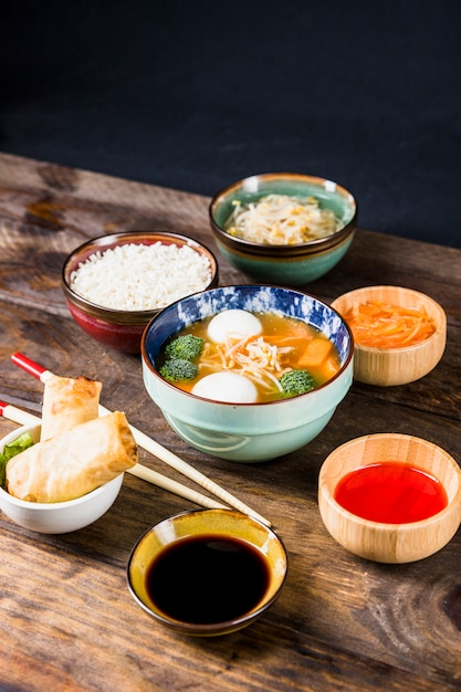 Rice; spring rolls; sauces; beans sprout; grated carrots with fish ball soup on desk against black background Free Photo