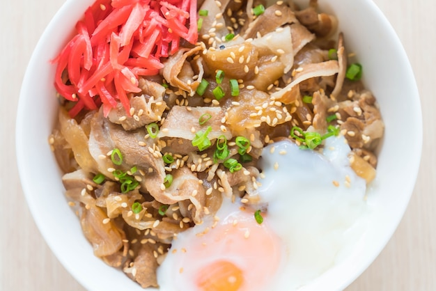 Rice topped with slice pork and onsen egg Free Photo
