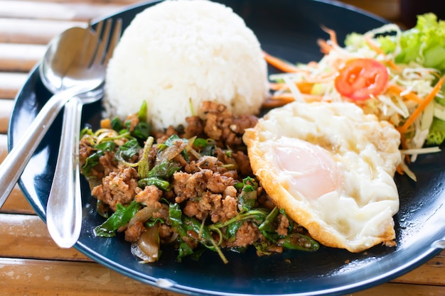 Rice topped with stir-fried pork and basil Premium Photo
