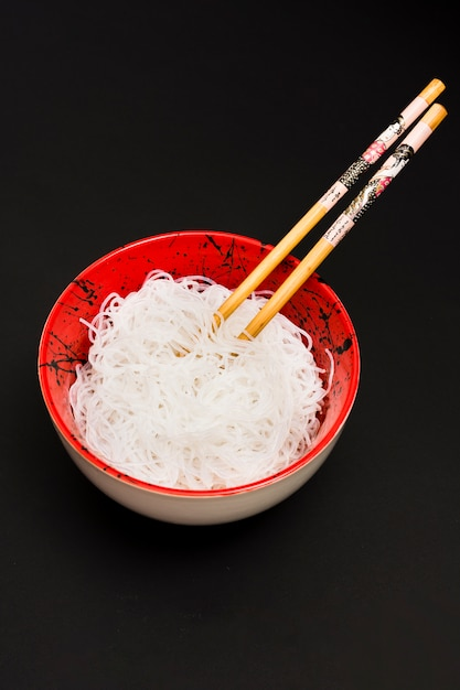 Rice vermicelli in bowl with chopstick over black surface Free Photo