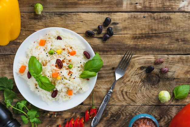 Rice with beans on plate with fork on wooden backdrop Free Photo