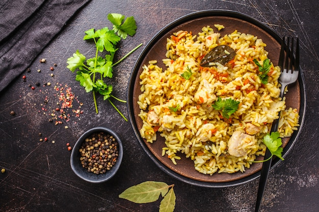 Rice with chicken in a black plate on a dark background, top view. Premium Photo