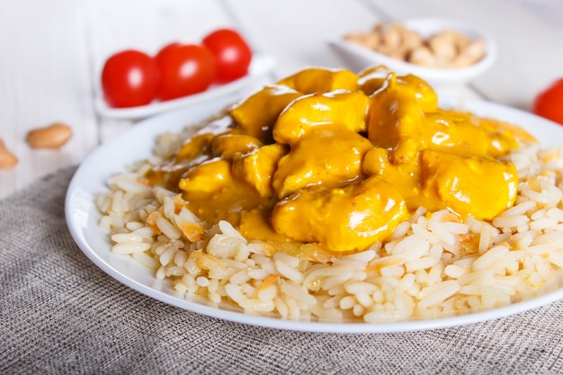 Rice with chicken curry sauce with cashew on white wooden background. Premium Photo