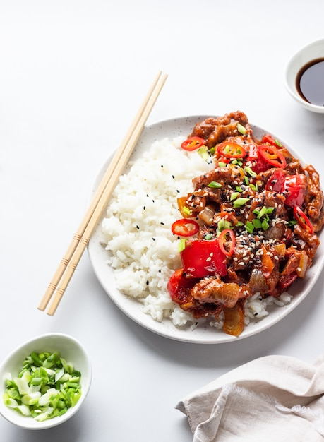 Rice with stir fried pork, vegetables and green onion Premium Photo