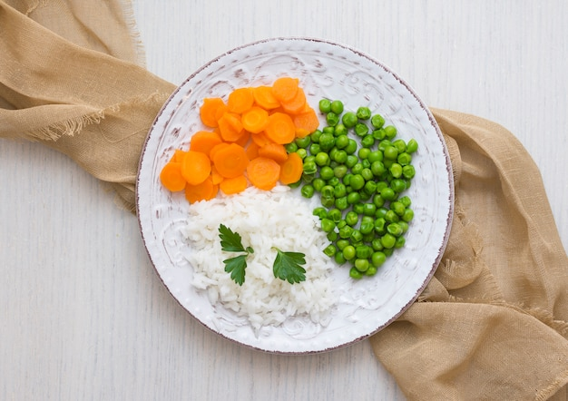 Rice with vegetables and parsley on plate with cloth Free Photo