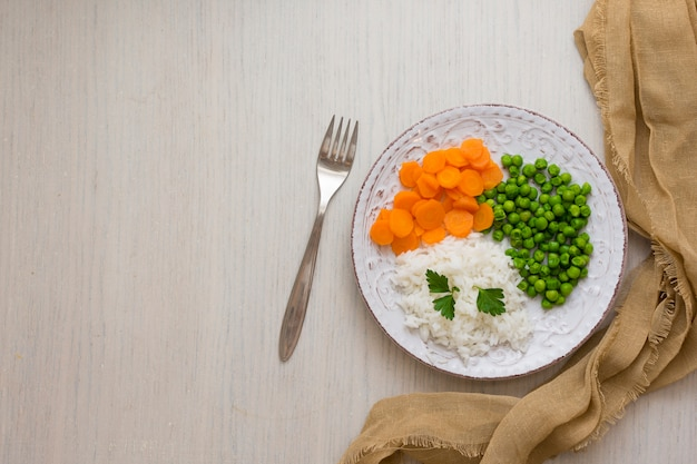 Rice with vegetables and parsley on plate with fork Free Photo