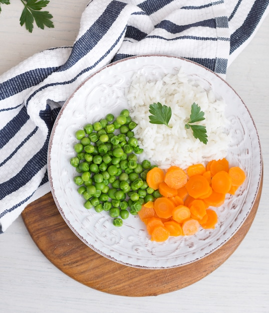Rice with vegetables and parsley on wooden board near napkin Free Photo
