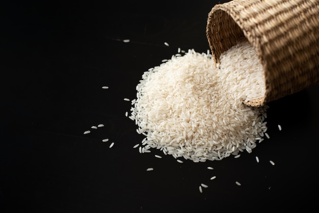 Rice and wooden spoon on black background Premium Photo
