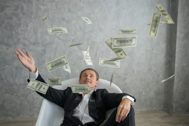 Rich businessman lying in bathtub filled with dollar banknotes. success business concept. Premium Photo