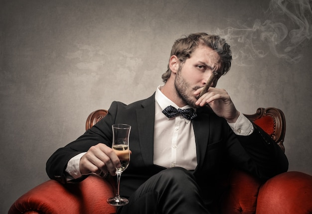 Rich elegant man smoking and drinking Premium Photo