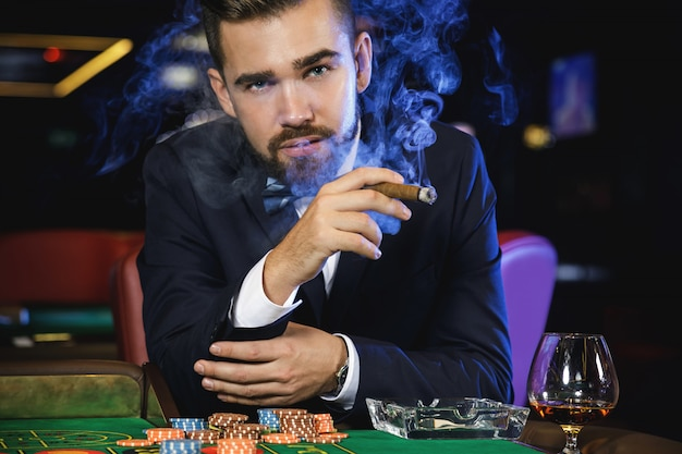 Rich handsome man smoking cigar in the casino Premium Photo