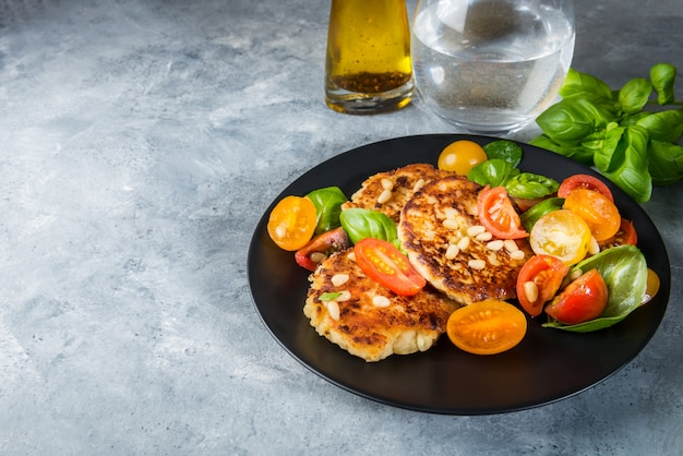 Ricotta pancakes with spinach, tomatoes, basil and pine nuts sal Premium Photo