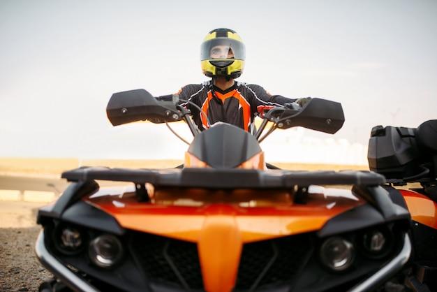 Всадник в шлеме и снаряжении на квадроцикле, вид спереди, крупным планом. водитель квадроцикла мужского пола, езда на квадроцикле Premium Фотографии