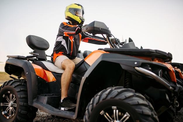 Всадник в шлеме на квадроцикле, вид спереди, крупным планом Premium Фотографии