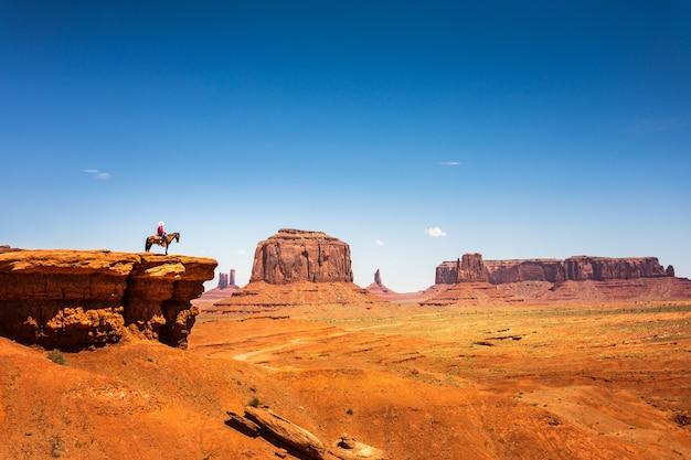 Всадник на лошади на вершине горы из песчаника Premium Фотографии