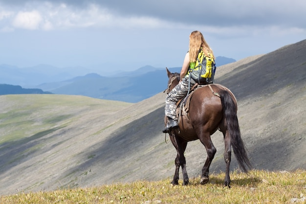 Rider with backpack on horseback Free Photo