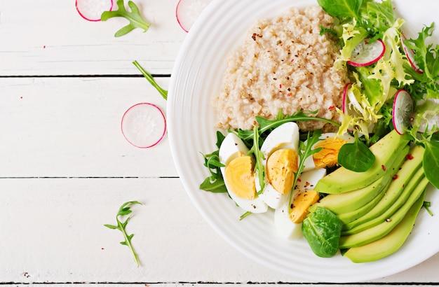 健康的な朝食。食事メニュー。オートミールのおridgeとアボカドのサラダと卵。上面図 無料写真