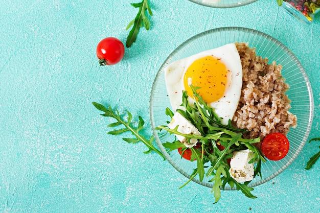 明るい背景に卵、フェタチーズ、ルッコラ、トマト、ソバのおridgeと健康的な朝食。適切な栄養。食事メニュー。平干し。上面図 無料写真