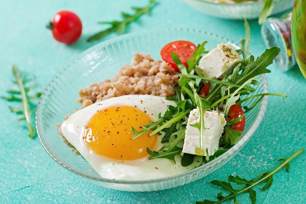 明るい背景に卵、フェタチーズ、ルッコラ、トマト、ソバのおridgeと健康的な朝食。適切な栄養。食事メニュー。 無料写真