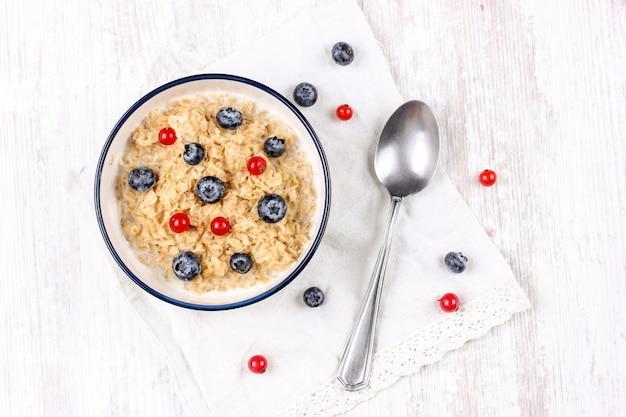 新鮮なブルーベリーと赤スグリの実のオートミール。ダイエット食品-スプーンで皿にオートミールのおridge。 Premium写真