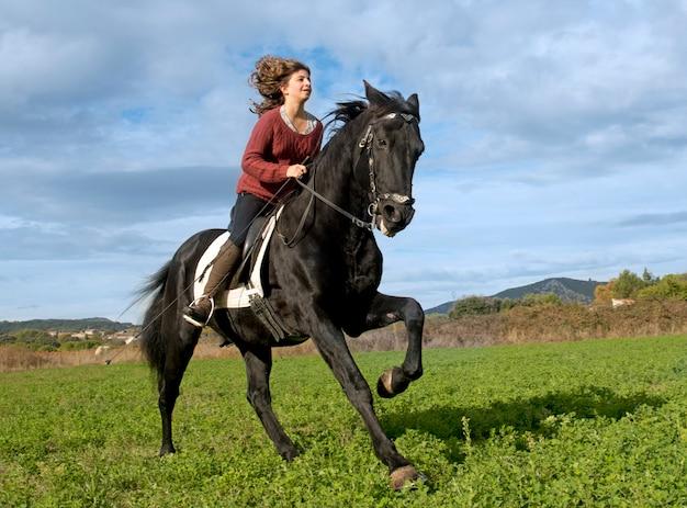 Езда девушка и черный жеребец Premium Фотографии