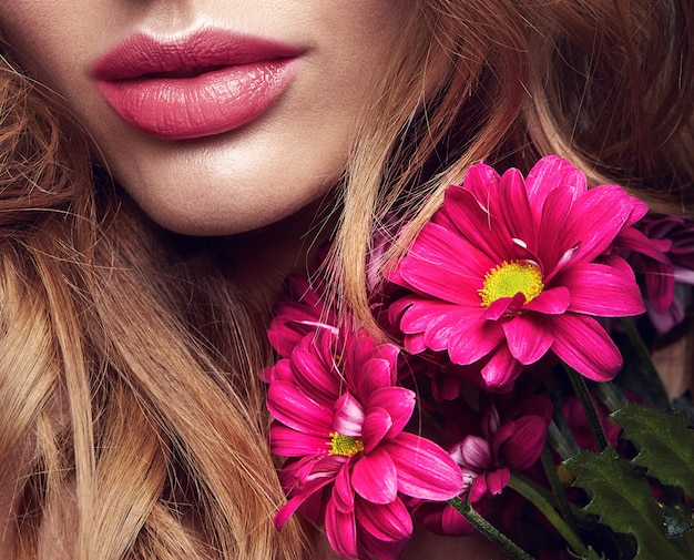 自然化粧品と明るいсrimson菊の花のポーズで完璧な肌を持つ若いブロンドの女性モデルの美容ファッションポートレート 無料写真
