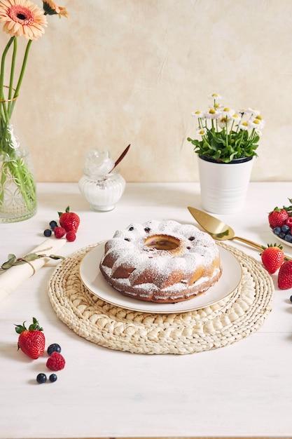 白い表面の白いテーブルに果物と粉のリングケーキ 無料写真