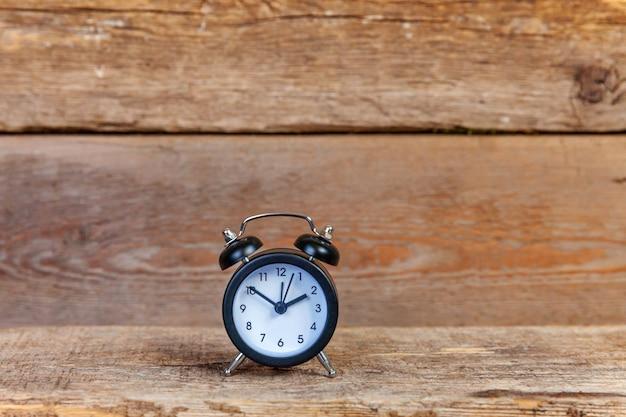 Звонящий двойной колокол винтажный классический будильник на старом потрепанном деревенском деревянном фоне Premium Фотографии