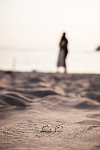 背景に新郎新婦とビーチでリング Premium写真