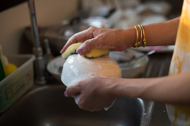 ランニング水の下で女性rinsing料理の手を閉じます Premium写真