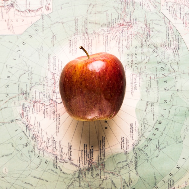 Ripe apple on map Free Photo