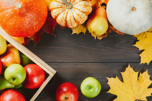 Ripe apples in a box with pumpkins, apples and pears on dark wooden . Premium Photo