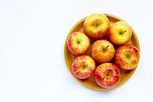 Спелые яблоки на желтой тарелке на белом фоне. копировать пространство Premium Фотографии