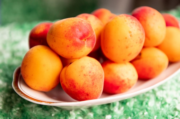 Ripe apricots in a plate on a green background Premium Photo