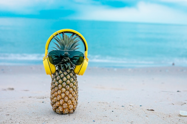 Ripe attractive pineapple in stylish mirrored sunglasses and gold headphones on sand against turquoise sea water. tropical summer vacation concept. Premium Photo