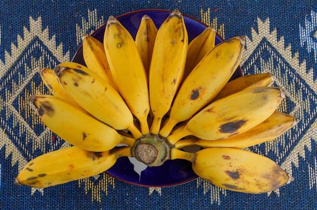 Le banane mature in un piatto piatto giacevano su un kilim a mosaico Foto Gratuite