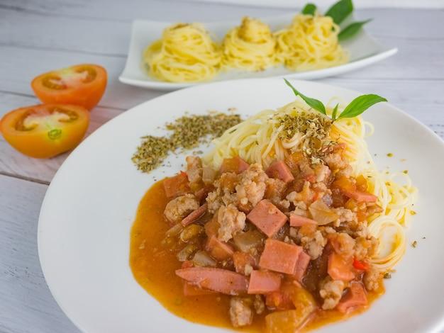 Ripe cooked pasta spaghetti tomato sauce oregano in white plate Premium Photo